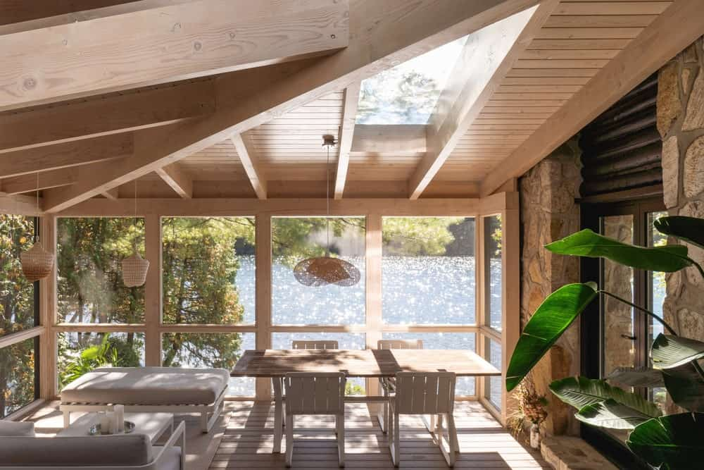 This is interior look at the glass-enclosed porch of the house with an outdoor dining area on the side that has a view of the lake.