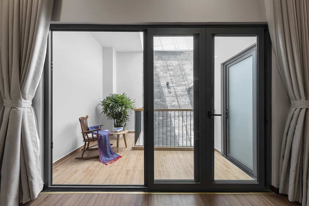 A few steps from the indoor balcony is a set of sliding glass doors with dark frame that makes it stand out against the light tone of the walls.