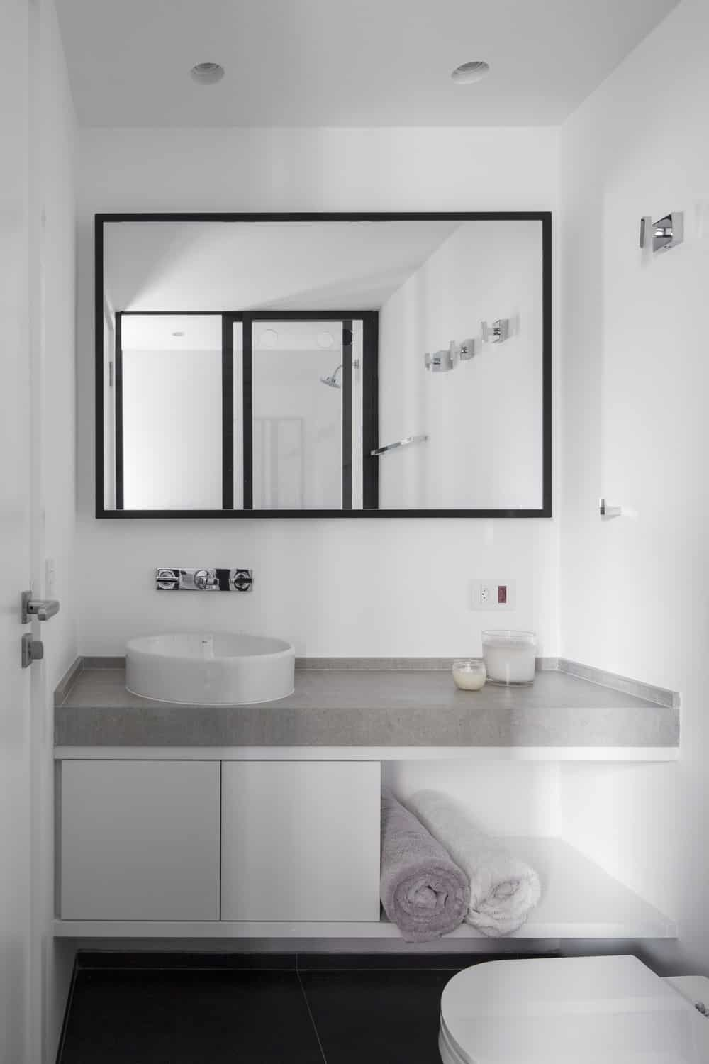 This is a look at the modern floating vanity of the bathroom topped iwth a mirror by the toilet.