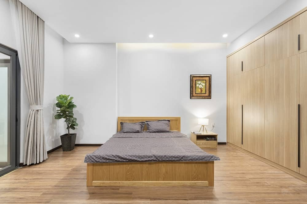 The spacious bedroom has a wooden platform bed that blends with the hardwood flooring but contrasts the gray cushion and pillows.