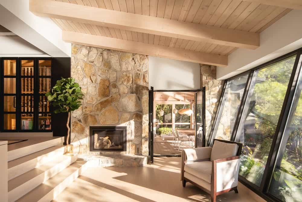 Upon entry of the glass doors of the porch, you are welcomed by this cozy interior that has stone walls, a fireplace and a comfortable cushioned arm chair.