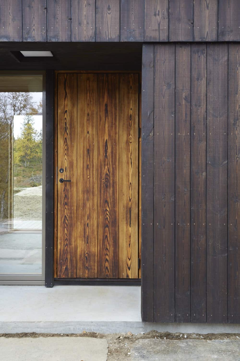 This is a close look at the main door of the house with a slightly lighter tone and a large glass panel on its side to let in natural lighting.