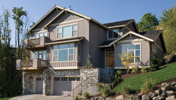 An alternate exterior with gray horizontal and vertical siding, stone accents, and tiled roofs.