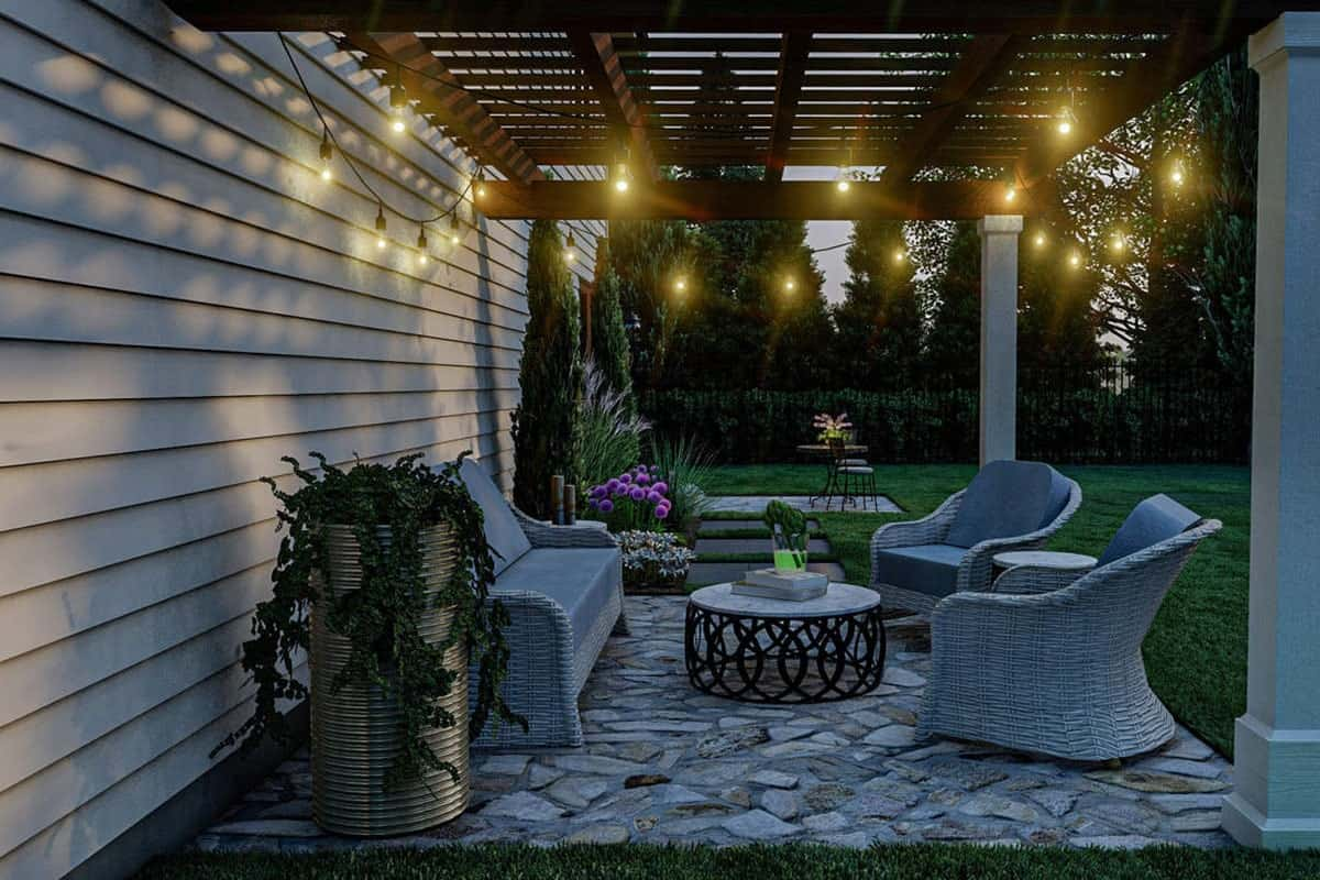 String lights hanging from the pergola roof illuminate the rear patio.