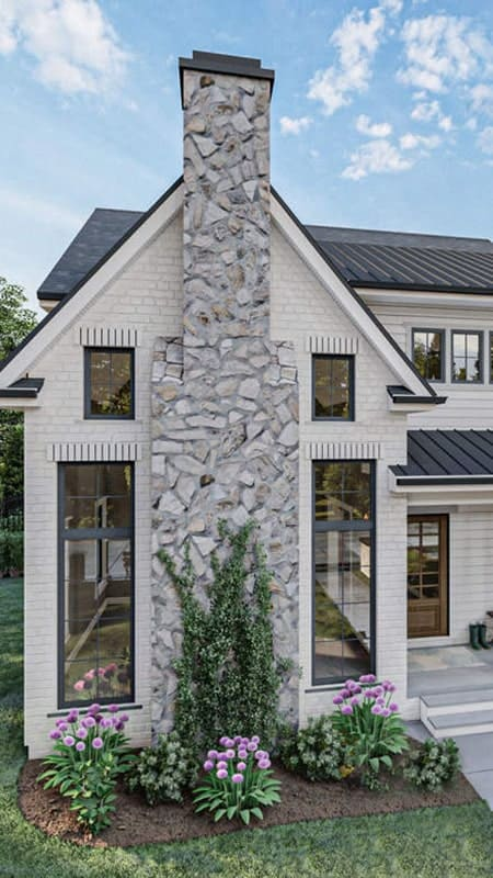 A closer look at the home facade showcasing its white brick cladding, stone chimney, and tall glass windows.