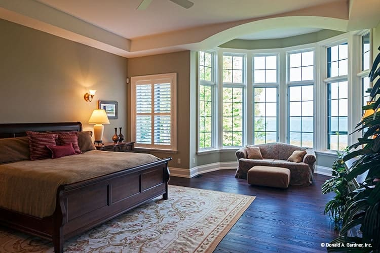 Primary bedroom with a dark wood bed, a classic area rug, and a bayed sitting area filled with a classic sofa and ottoman.
