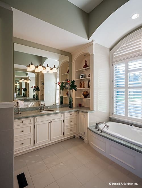 The primary bathroom has white vanities and a drop-in bathtub fixed under the louvered window.