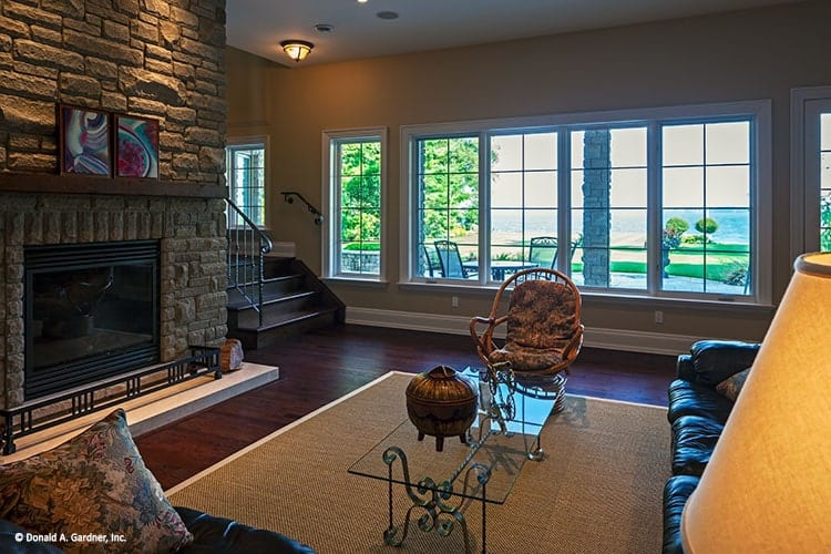 Recreation room with a stone fireplace, leather seats, and a glass top coffee table over a jute area rug.