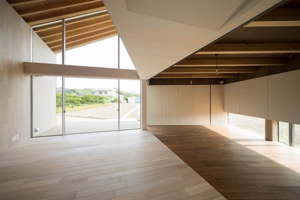 This is a look at the interior of the house with wooden tones on its walls, beamed ceiling and hardwood flooring.