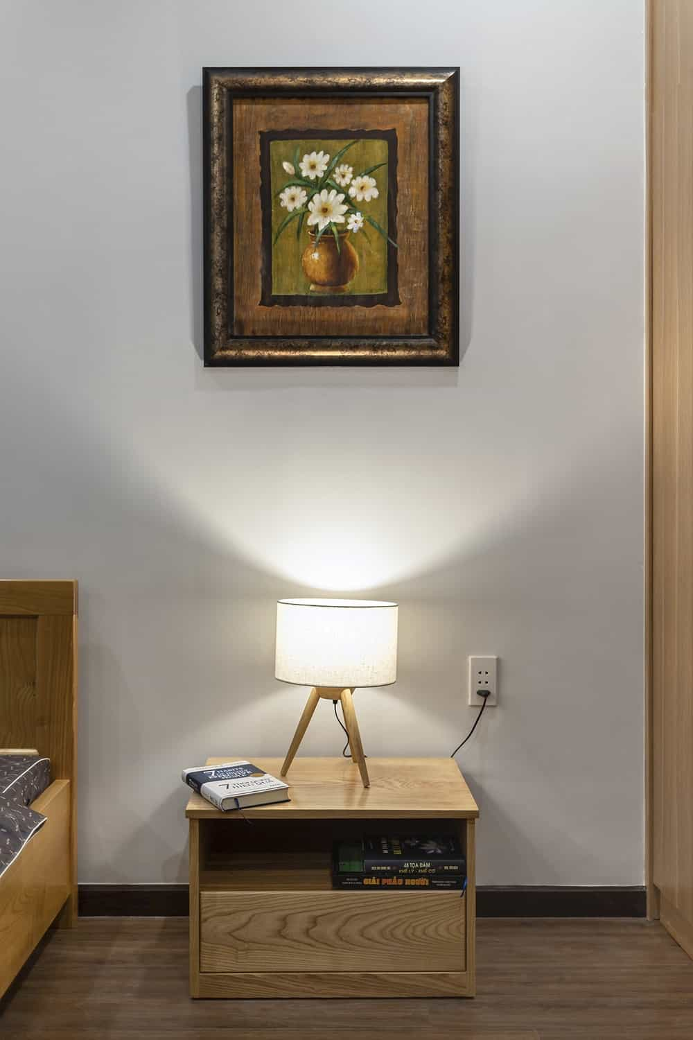 This is a close look at the wooden bedside table topped with a table lamp and a painting.