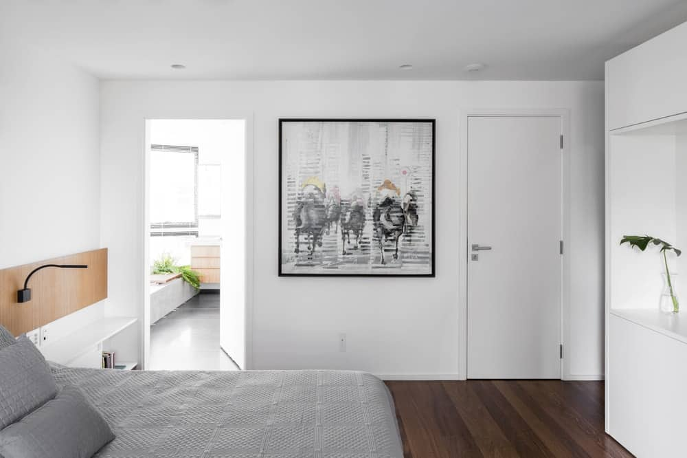 On the side of the bed is the door access to the bathroom adorned with a large framed artwork.