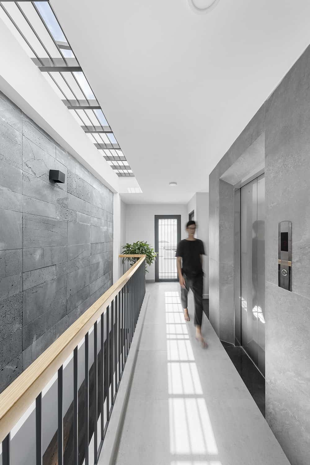 This is a close look at the hallway and indoor balcony of the third floor and the house's modern stainless steel elevator.
