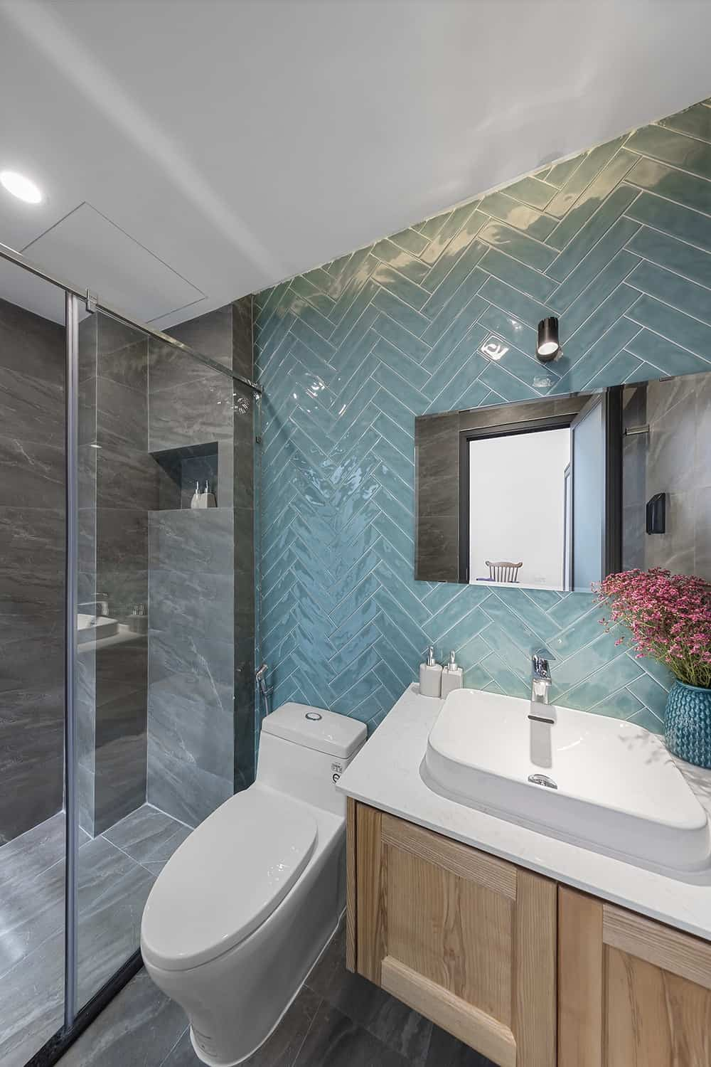 The bathroom has a light blue herringbone wall that contrasts the white porcelain toilet and sink. On the far side is the glass-enclosed shower area with dark gray tones,