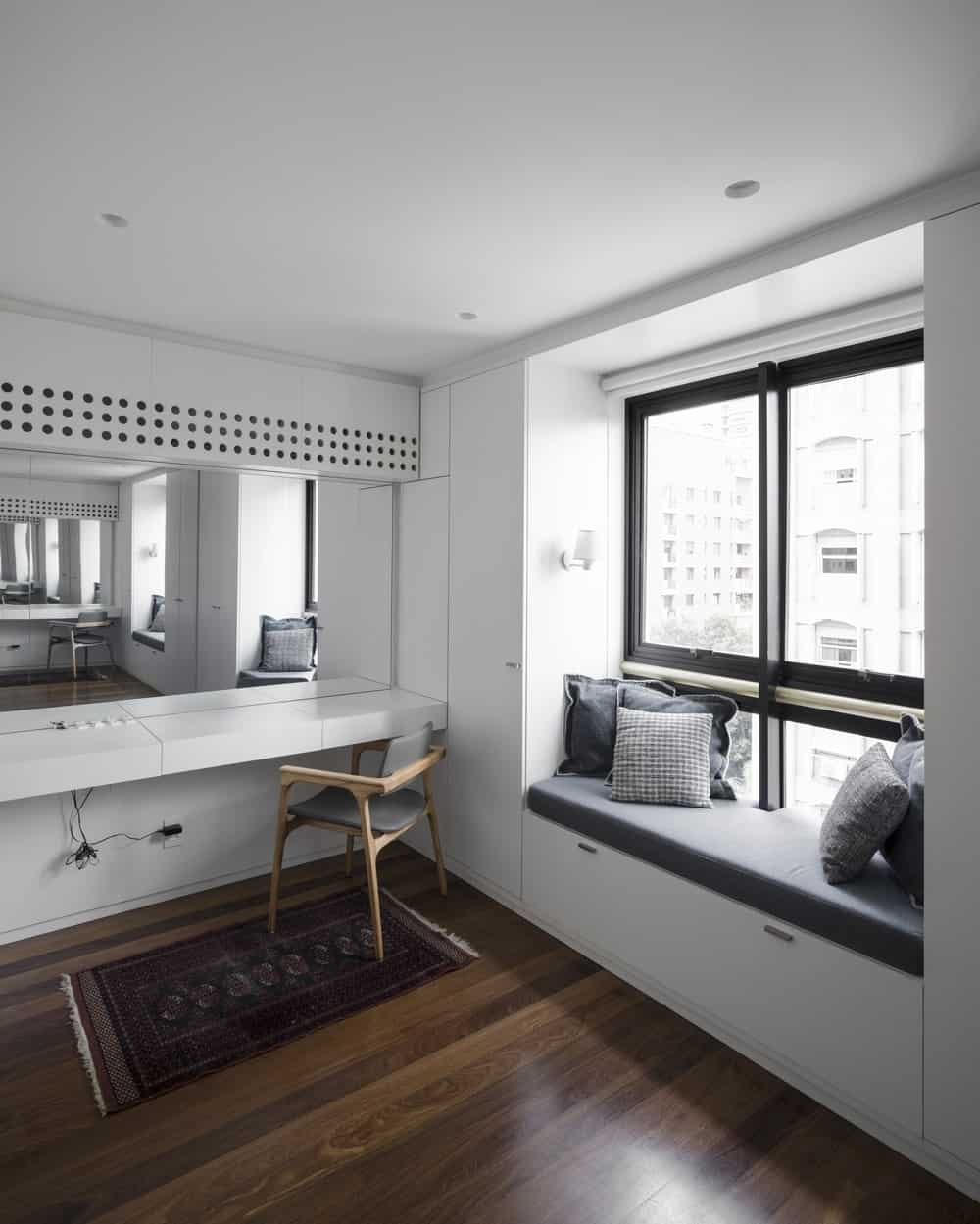 This is a vanity area with a large mirror, a counter and a built-in cushioned bench by the window.