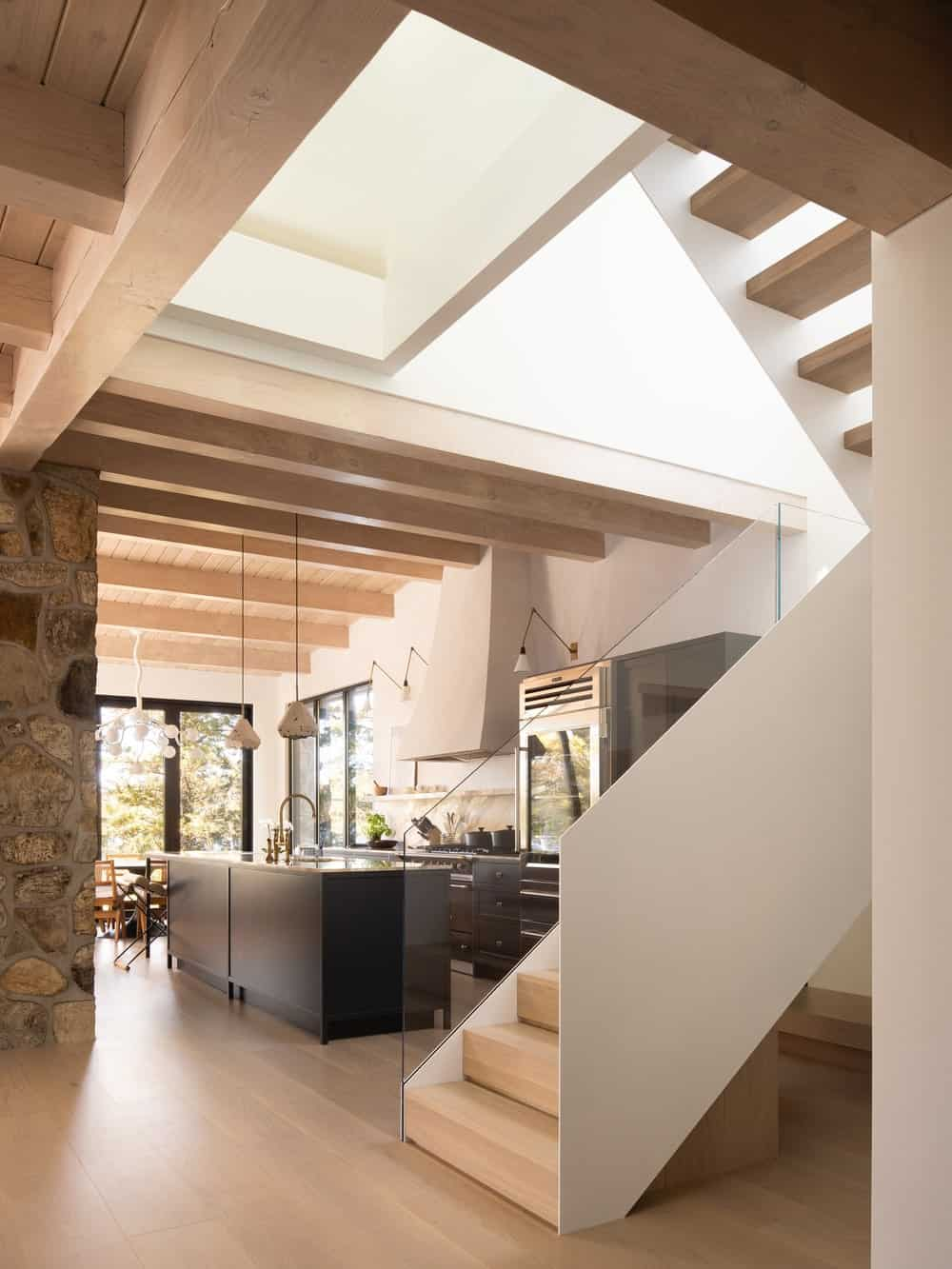 A few steps from the dark kitchen island is the staircase with wooden steps to match the hardwood flooring and the walls to match the rest of the house interiors.