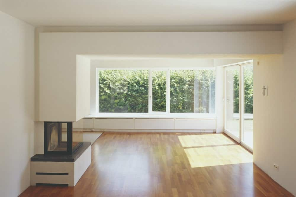 This is a spacious and airy section of the house with large glass walls and a modern fireplace.