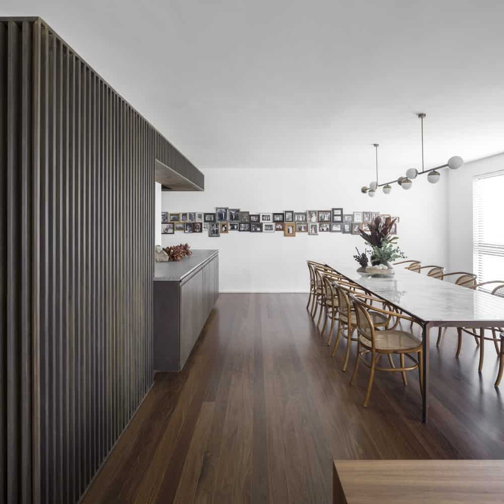 This is a look at the dining area and the kitchen on a dark hardwood flooring that contrasts the bright ceiling.