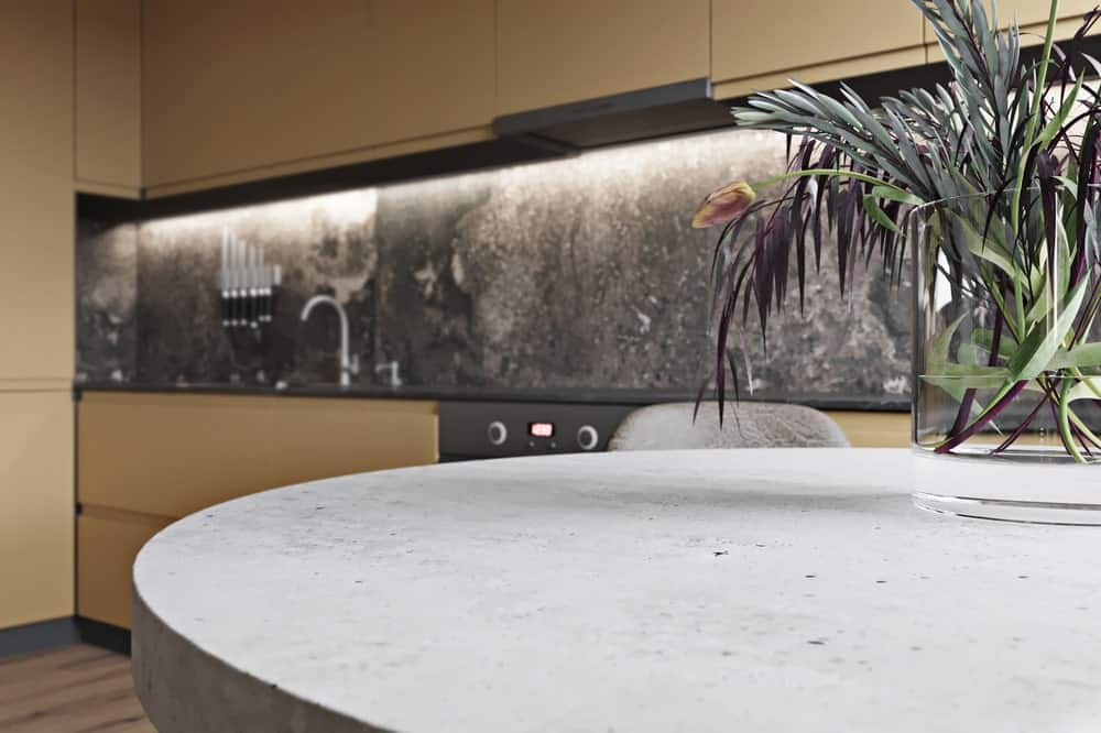 This is a close look at the round dining table of the dining area and gives a view of the dark marble countertop and backsplash of the kitchen on the side with a modern lighting above it.