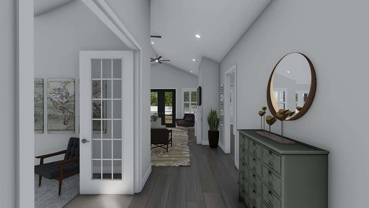 The foyer has a drawer cabinet topped with wooden decor and a round mirror.