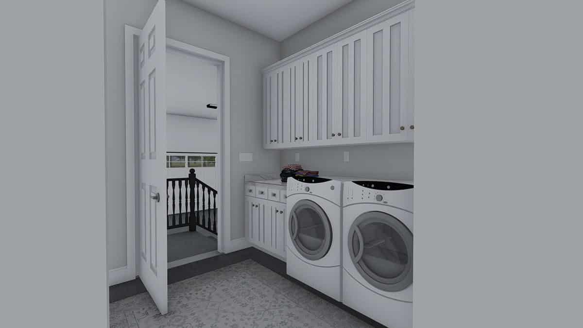 The utility room is equipped with white front load appliances and custom cabinets.