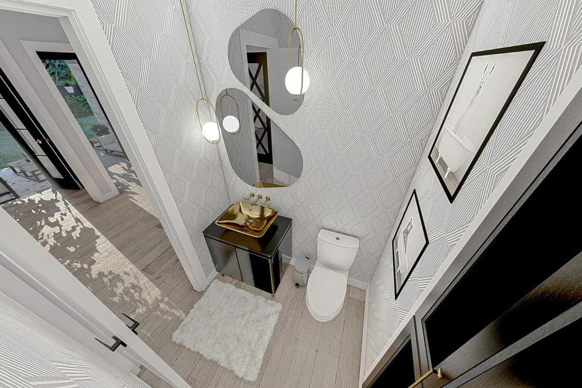 Powder room with a toilet and a sink vanity complemented with unique mirrors and brass pendants.