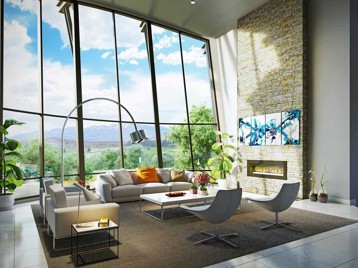 Living room with modern seats, a stone fireplace, and floor to ceiling glass windows overlooking the outdoor scenery.