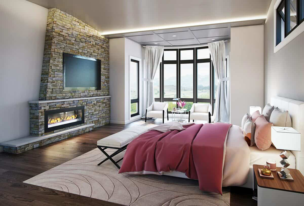 Primary bedroom with white upholstered bed, a modern fireplace, and a bright sitting area filled with sleek armchairs.