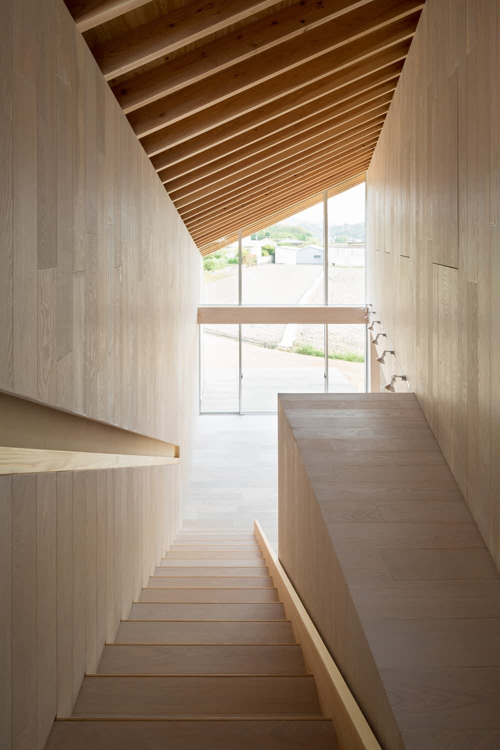 This is a look at down the staircase with the same wooden tone as the rest of the interiors. It has a wall depression that works as the banisters.