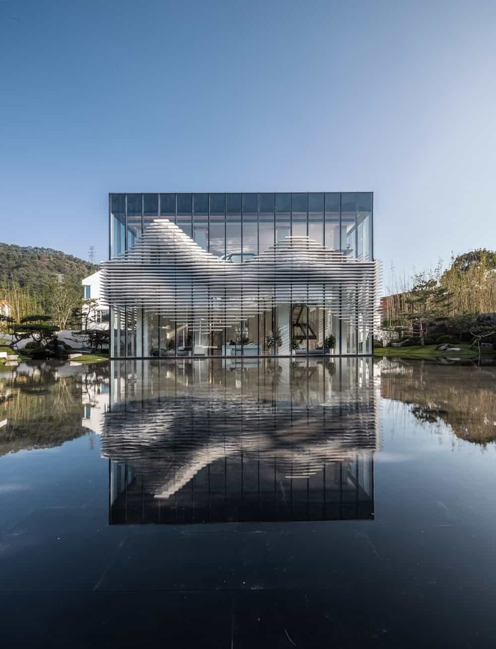 The large glass building and its unique design are augmented by the water landscape that reflects the structure.