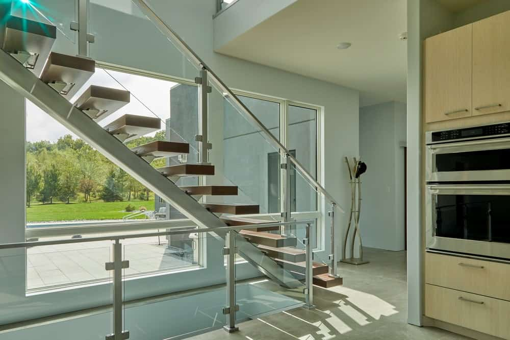 This is a closer look at the modern staircase with glass walls on its railings.