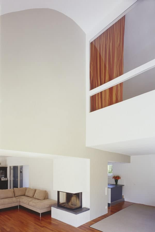 This is a look at the living room area with a tall ceiling paired with an indoor balcony and white tall walls.