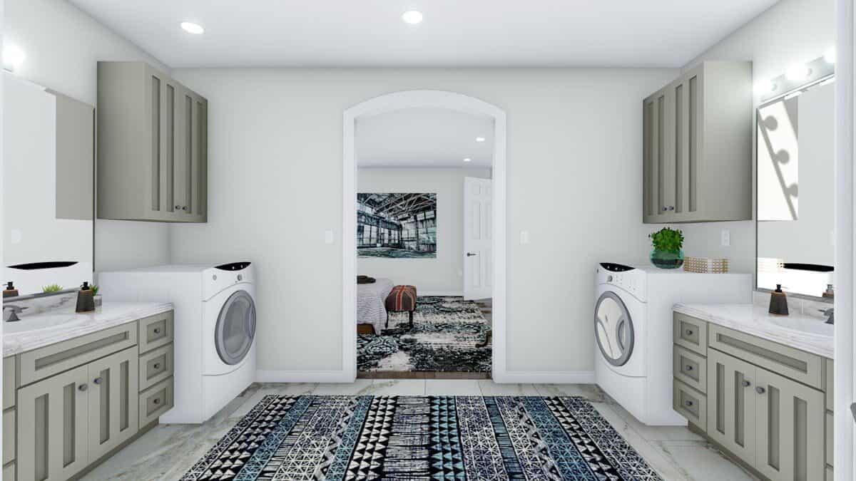 A farther view of the primary bath showing the facing vanities and washing machines flanking a large patterned rug.