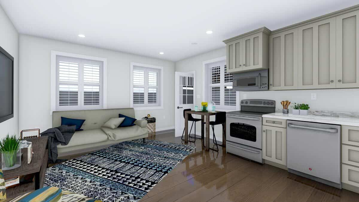 Studio with leather sofa, a wooden dining set, slate appliances, and cream cabinets.