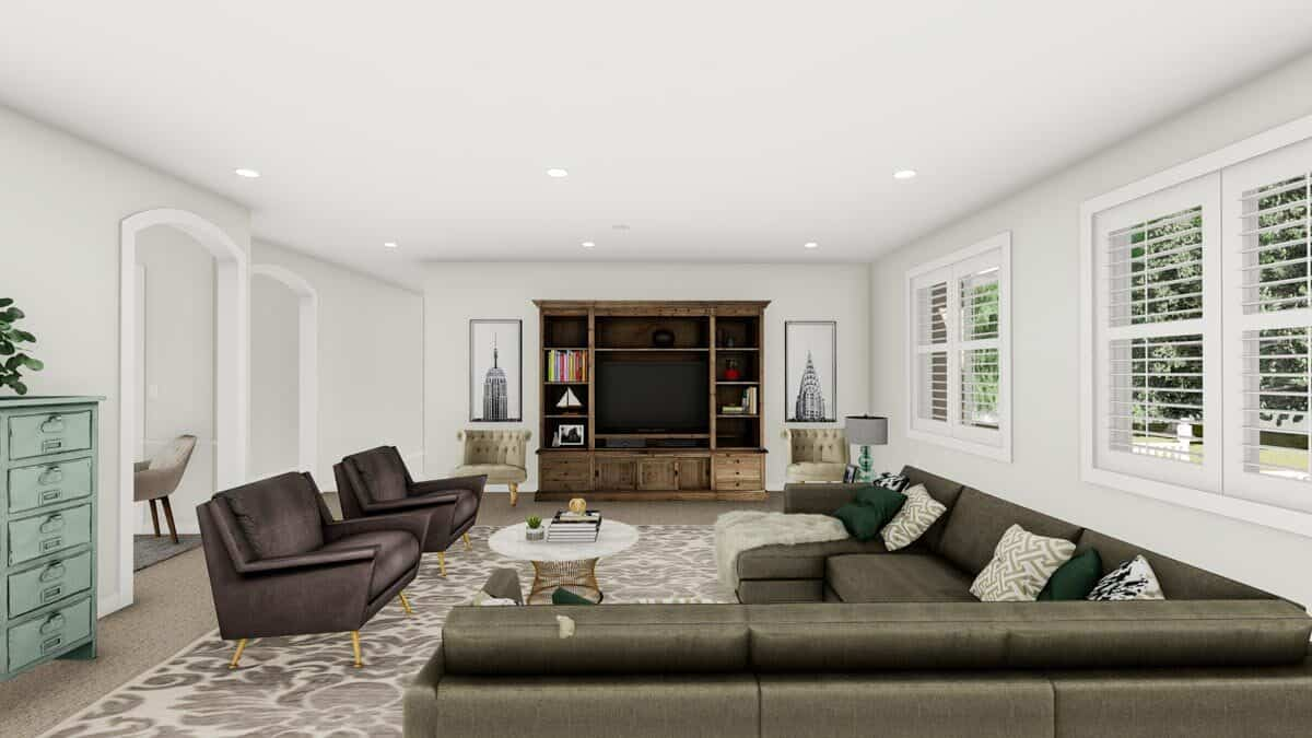A large built-in cabinet flanked by tufted armchairs and artworks complete the family room.