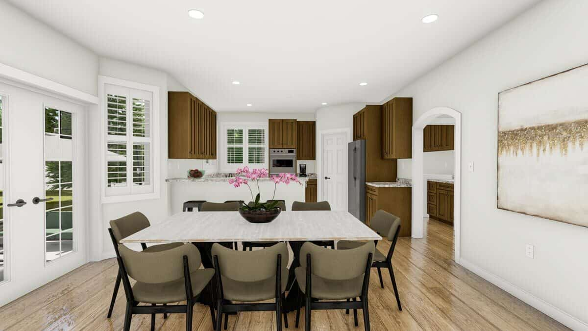 The dining area has round back chairs and a rectangular dining table topped with a flower vase.