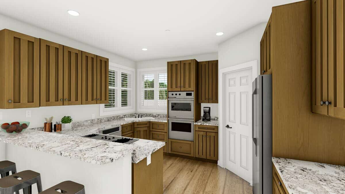 The kitchen is equipped with slate appliances, granite countertops, custom wooden cabinetry, and a two-tier peninsula.