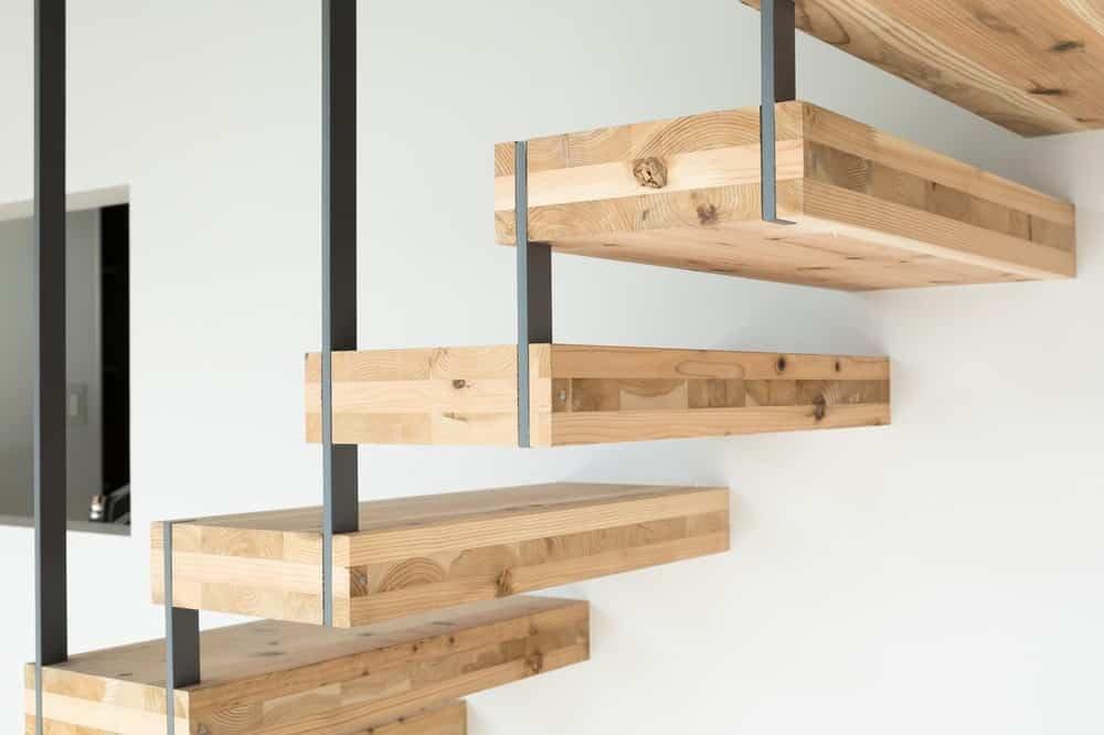 This is a closer look at the modern staircase that has floating wooden steps and wrought iron railings.