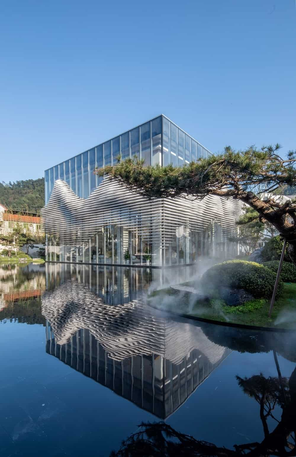 The water structure that augments the structure is softened up further by the zen-like tree.