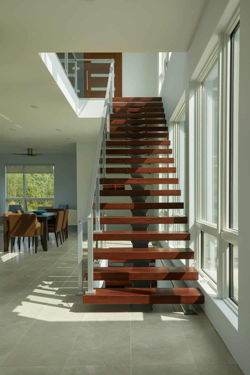 The staircase has dark wooden steps that appear to float with its glass elements on the sides.