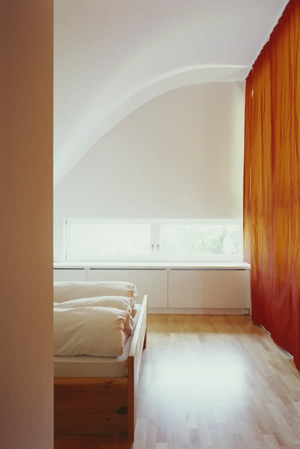 The bedroom has light hardwood flooring that is brightened by the white walls and ceiling illuminated by the natural lighting.
