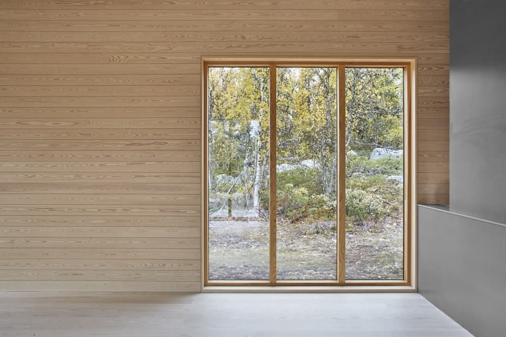 This is a look at the interiors of the house with light wooden tones to its walls and glass walls.