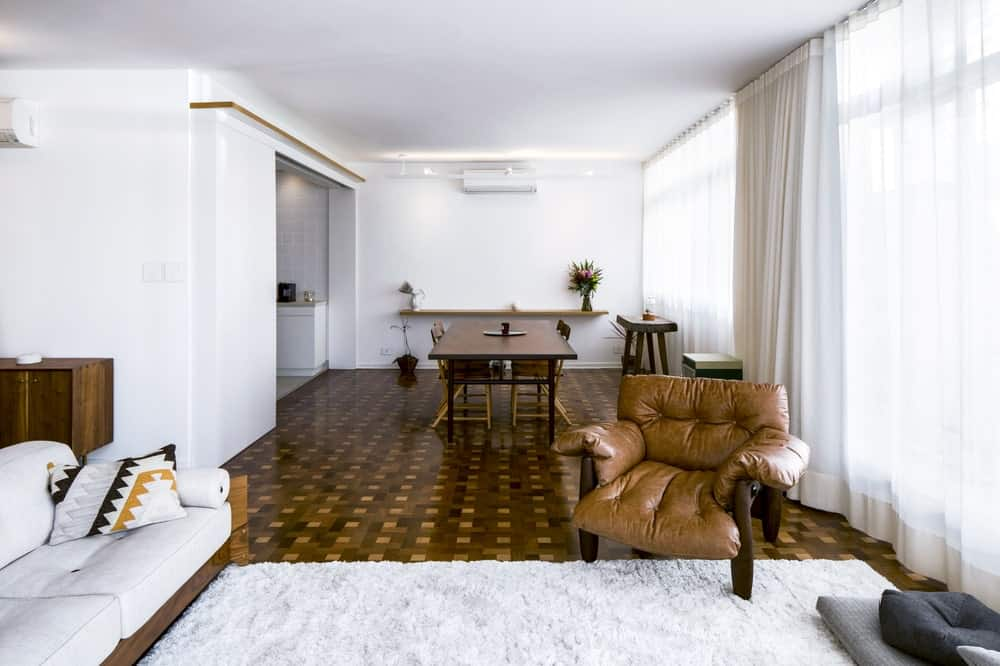 The brown leather armchair stands out against the white area rug of the living room but matches the hardwood flooring.