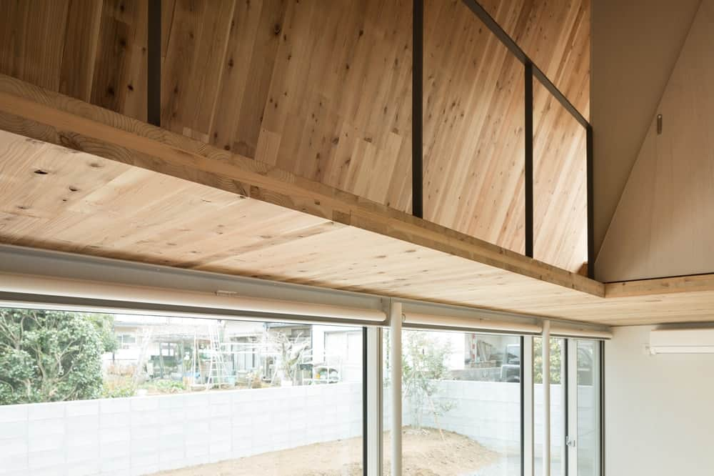 This is a closer look at the glass walls that bring in natural lighting. Above this is a wooden walkway of the second level with railings.