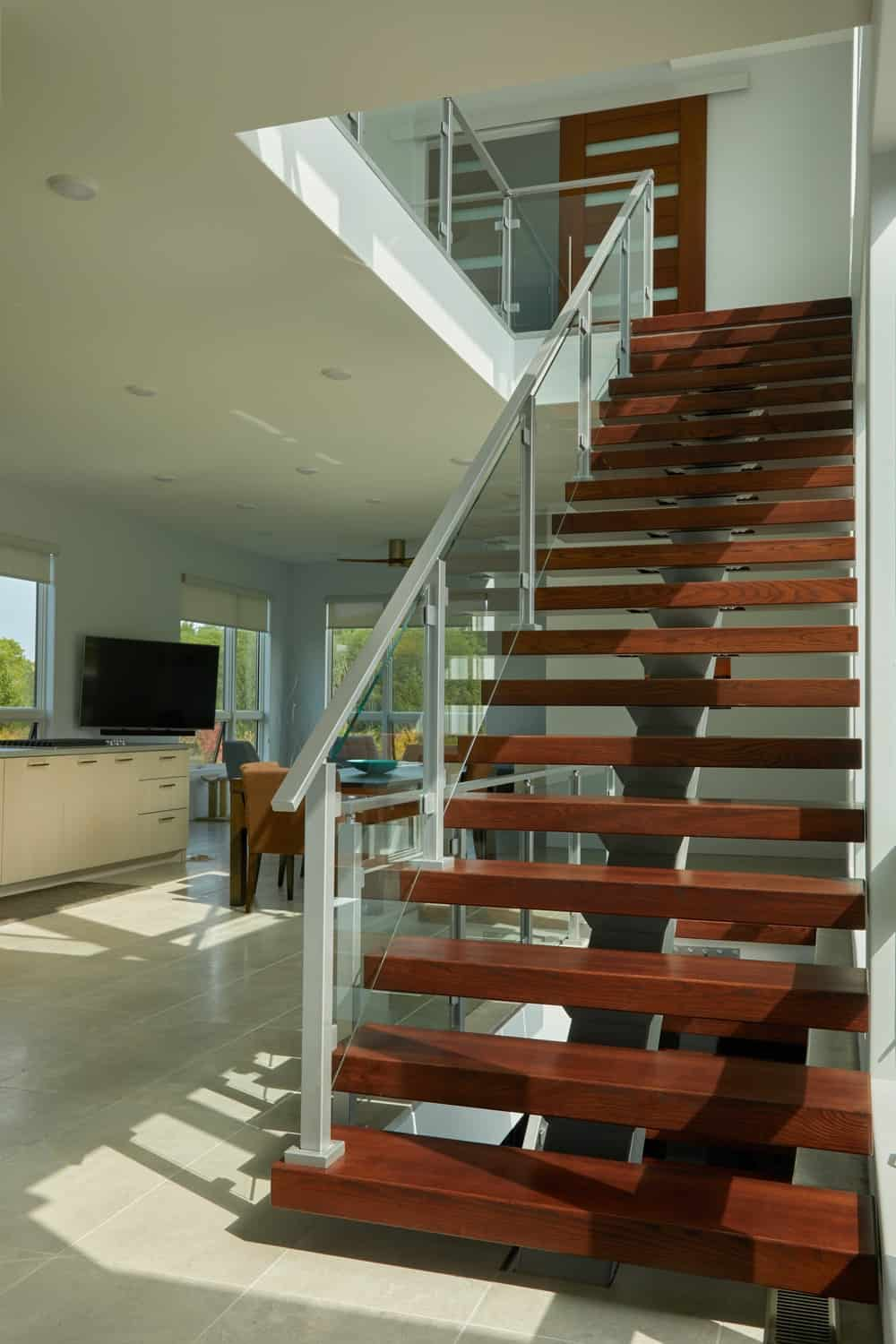 The glass walls of the staircase also gives a full view of the kitchen and dining area on the far side.