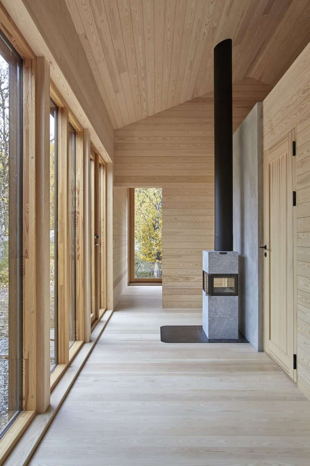 Upon entry of the house, you are welcomed by this simple foyer with a warm modern fireplace on the side of the main wooden door.