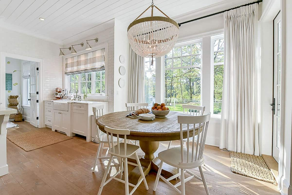 Breakfast nook with white chairs, round dining table, and a beaded chandelier.