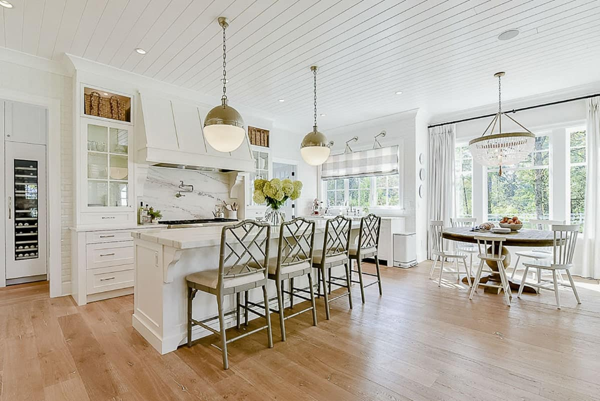 The eat-in kitchen has light hardwood flooring and a shiplap ceiling that matches the white cabinets.
