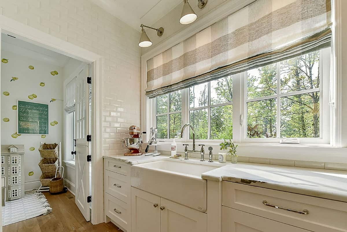 The butler's pantry has a farmhouse sink, marble countertops and white framed windows dressed in checkered roman shades.