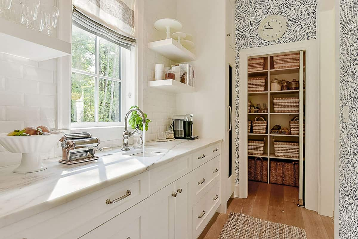 A door on the right side opens to the walk-in pantry filled with built-in shelves and storage baskets.