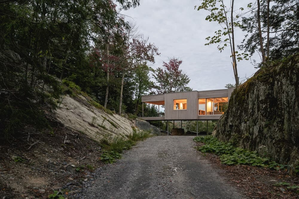 This is a view of the house from the wide graveled driveway leading to the house with light wooden tones.